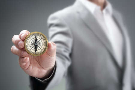 Businessman holding compass showing direction concept for guidance, strategy and business orientation Foto de archivo