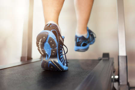 gym: Man running in a gym on a treadmill concept for exercising, fitness and healthy lifestyle
