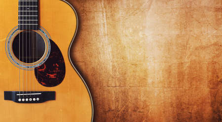 grunge music background: Acoustic guitar resting against a blank grunge background with copy space
