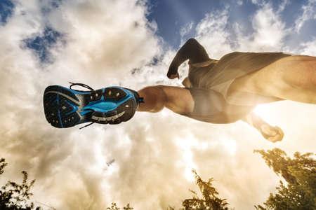 ライフスタイル: 屋外の運動、フィットネス、健康的なライフ スタイルのためのランナーのコンセプトのもと低角度表示をクロスカントリー実行