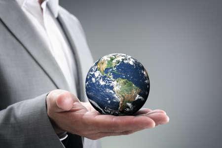 通訊: 商人舉行的世界在他的手中理念,為全球商業,通信,政治或環境的保護地球的圖像由NASA提供的手掌在http:visibleearth.nasa.gov 版權商用圖片