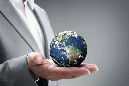Businessman holding the world in the palm of his hands concept for global business, communications, politics or environmental conservation