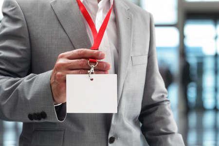Hombre de negocios en una exposición o conferencia que muestra una identidad de seguridad tarjeta de presentación en blanco en una cuerda de seguridad