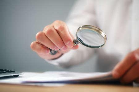 Zakenman het lezen van documenten met vergrootglas concept voor het analyseren van een financiële overeenkomst of juridisch contract Stockfoto