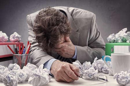 Überarbeitet, deprimiert und erschöpft Geschäftsmann an seinem Schreibtisch mit einem Stapel von Arbeit oder Konzept für Frustration, Stress und Schriftsteller Block