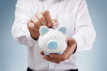 business savings: Businessman inserting a coin into a piggy bank concept for business savings, investment or banking