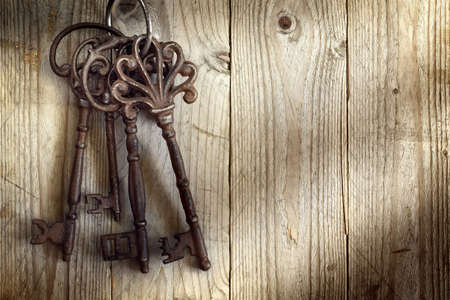Old skeleton keys hanging against a wooden background