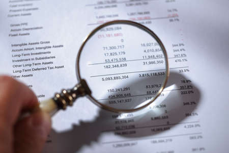account statements: Businessman holding a magnifying glass on a financial report concept for finance, balance sheet, tax or accounting