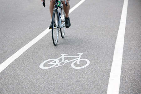 road cycling: Commuter riding a bicycle on a city cycle lane or path across white painted bike symbol