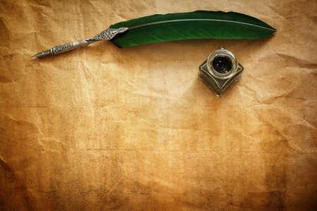 pluma de escribir antigua: Quill pluma y tinta bien apoyada en el papel de pergamino en blanco, con copia espacio para el mensaje