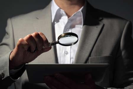 Obchodník držel zvětšovací sklo a digitální koncept tabletu pro vyhledávání na internetu, hledání zaměstnání nebo analyzování účtů