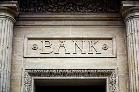 loans: Old bank sign engraved in stone or concrete above the door of financial building concept for finance and business