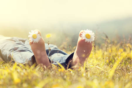 child feet: Child with daisy between toes lying in meadow relaxing in summer sunshine