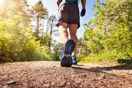 early summer: Man jogging or waking outdoors on a footpath or trail concept for healthy lifestyle, sport exercising, running and fitness