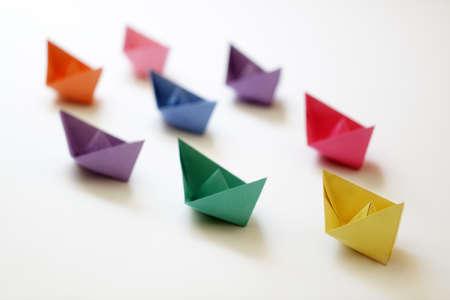 trabajo en equipo: Barcos de papel de varios colores siguiendo un concepto de barco líder de liderazgo, trabajo en equipo y el éxito de ganar