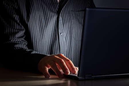 夜遅くまでインターネット中毒や作業後半人暗闇の中で机にノート パソコンを使用して 写真素材 - 45840381