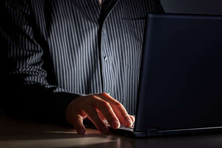 hacker: Late night internet addiction or working late man using laptop at a desk in the dark