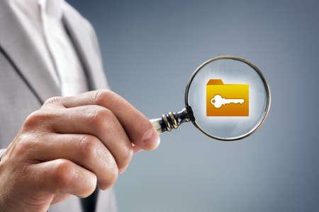 Zakenman met vergrootglas over bestand, map of document icoon concept voor de veiligheid inspectie, bescherming en vertrouwelijke gegevens