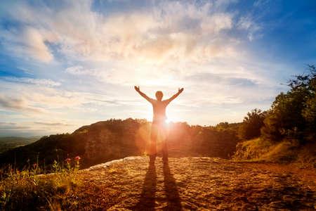 Silueta de un hombre con las manos levantadas en el concepto de la puesta del sol para la religión, el culto, la oración y la alabanza Foto de archivo