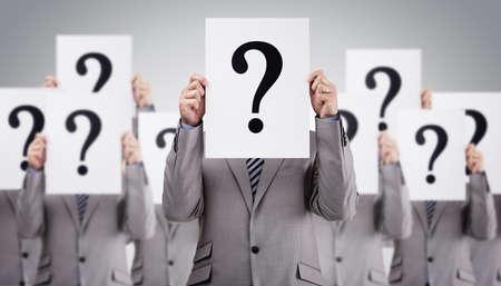 confundido: Colegas del asunto que llevan a cabo muestras de signo de interrogación en la parte delantera de su concepto caras para el reclutamiento, confusión o cuestionario Foto de archivo