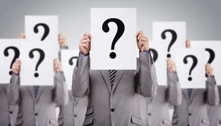 Business colleagues holding question mark signs in front of their faces concept for recruitment, confusion or questionnaire Standard-Bild