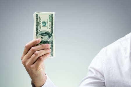 capitalist: Businessman holding one hundred dollar bills concept for paying, donation, business wealth, venture capitalist and banking Stock Photo