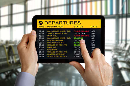 Digital tablet in airport with flight schedule and departure and gate information Stock Photo