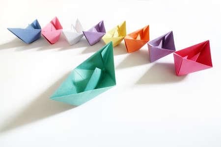lider: Barcos de papel de varios colores siguiendo un concepto de barco líder de liderazgo, trabajo en equipo y el éxito de ganar