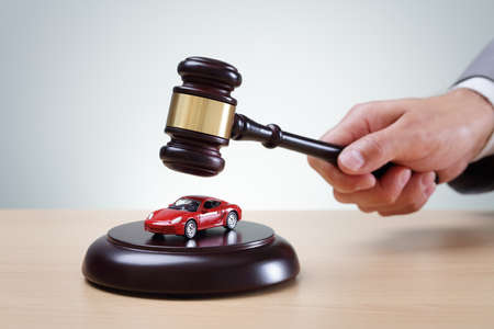 winning bid: Wooden gavel and red car concept for buying and selling at auction, speeding conviction, court appearance and prosecution Stock Photo