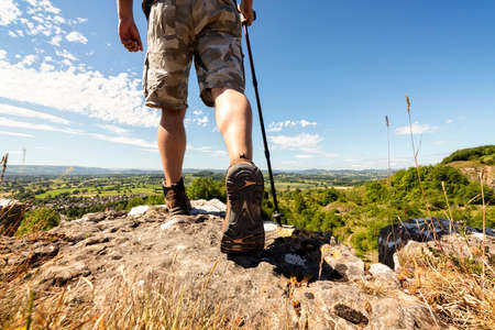 Hiker hiking on a mountain trail with distant views of countryside in summer sunshine Archivio Fotografico