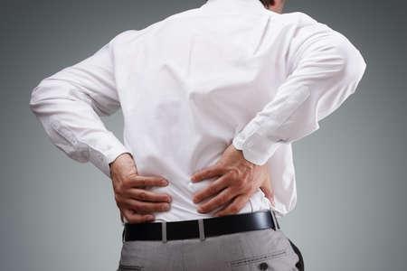 Rückenschmerzen Konzept Bücken in Schmerzen mit den Händen, den unteren Rücken
