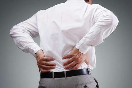 Backache concept bending over in pain with hands holding lower back Stockfoto