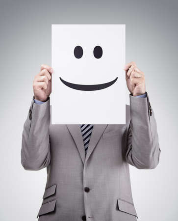 caras graciosas: Empresario de la celebraci�n y escondi�ndose detr�s de una tarjeta con la cara sonriente emoticono Foto de archivo