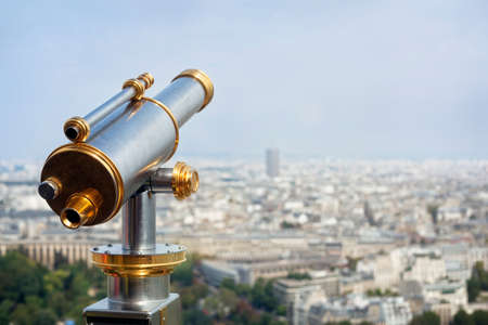 operated: Tourist coin operated telescope looking out over a city view