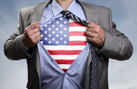 politics: Businessman in classic superman pose tearing his shirt open to reveal t shirt with the American flag concept for patriotism, freedom and national pride Stock Photo