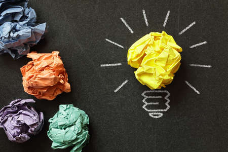 Inspiration concept crumpled paper light bulb metaphor for choosing the best idea Фото со стока