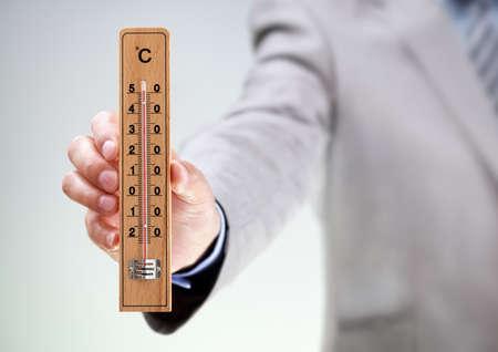 Zakenman die thermometer meten van hoge temperatuur concept voor klimaat, stress, onder druk of deadline