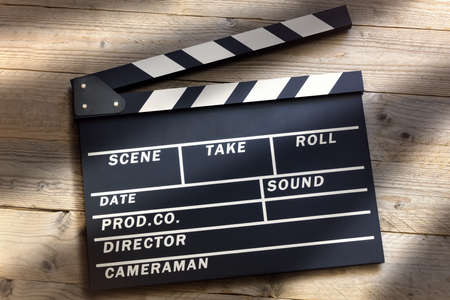 Film slate or movie clapper board on wood background Stockfoto