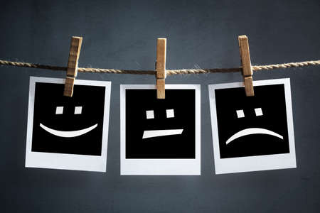 Glücklich, traurig und neutrale Emoticons auf Polaroid-Transfer Fotos hängen auf einer Wäscheleine