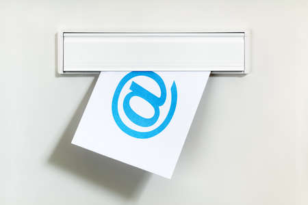 spam mail: E-mail symbol on letter being delivered through a letterbox concept for internet communication, social media and contact us