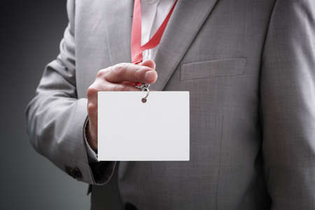 Homme d'affaires lors d'une exposition ou d'une conférence montrant un nom identité de sécurité carte blanche sur un cordon Banque d'images - 45840506