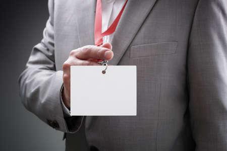 Homme d'affaires lors d'une exposition ou d'une conférence montrant un nom identité de sécurité carte blanche sur un cordon