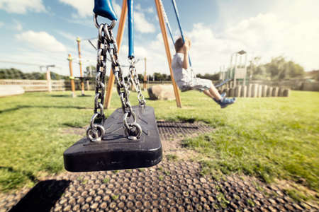 Lege speeltuin schommel met spelende kinderen op de achtergrond concept voor de bescherming van kinderen, ontvoering of eenzaamheid