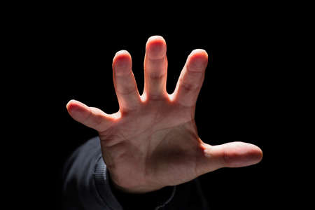 asustadotdo: Mano que alcanza desde la oscuridad y el acaparamiento o atacar concepto para el miedo, la violencia doméstica y el niño
