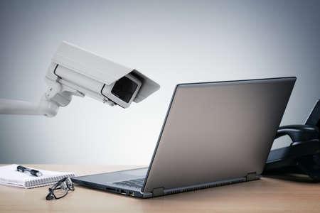 privacidad: Ordenador portátil siendo observado en la oficina por un concepto de cámaras de seguridad para la vigilancia de hermano mayor o internet en seguridad informática Foto de archivo