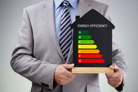 energy saving: Businessman holding house shape blackboard with chalk energy efficiency rating chart concept for performance, efficiency and environmental conservation Stock Photo