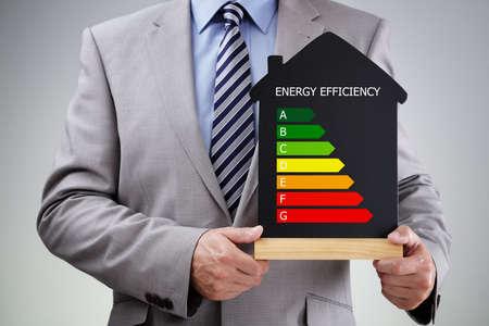 eficiencia: El hombre de negocios que sostiene la casa forma pizarra con el concepto gráfico de energía tiza índice de eficiencia para el rendimiento, la eficiencia y la conservación del medio ambiente Foto de archivo