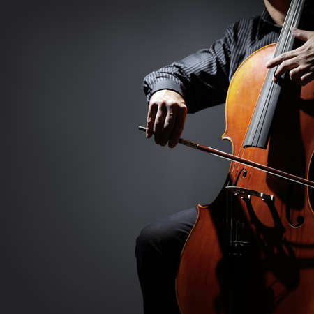 orquesta: Jugador del violoncelo o chelista actuando en una orquesta aislados con copia espacio