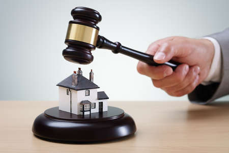 foreclosure: Bidding on a home, gavel and house concept for home ownership, buying, selling or foreclosure