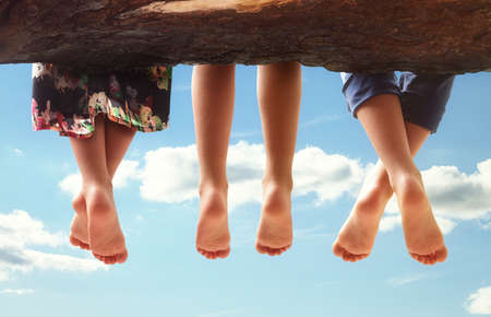 ragazze a piedi nudi: Tre ragazzi seduti in un albero penzoloni i piedi contro un cielo blu nel concetto estate per la famiglia, gli amici, spensierato e vacanze Archivio Fotografico